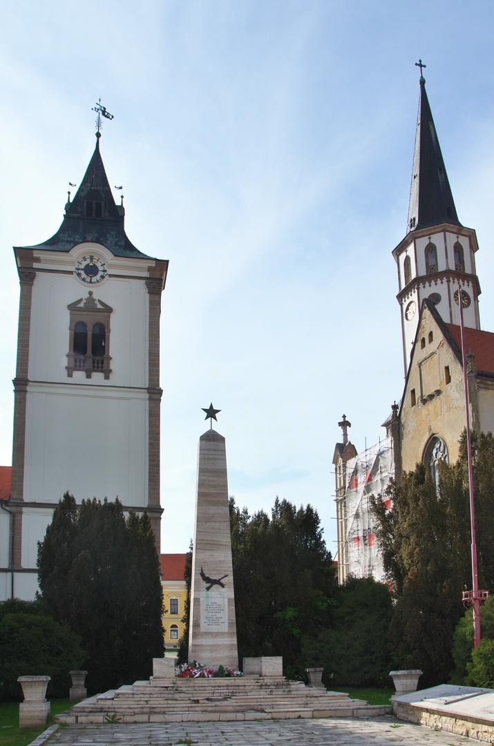 """Levoča - vlevo věž radnice, vpravo věž kostela sv. Jakuba, uprostřed poděkování """"červenej"""" armádě za osvobození"""